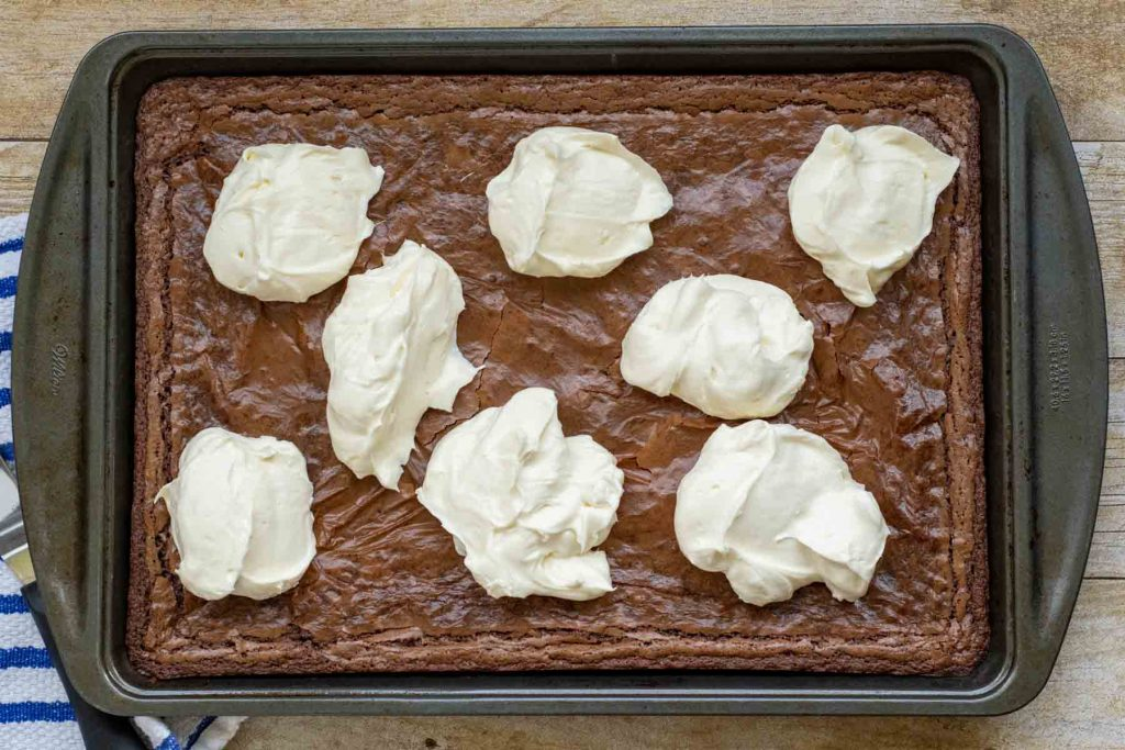 frosting dolloped over brownies before spreading