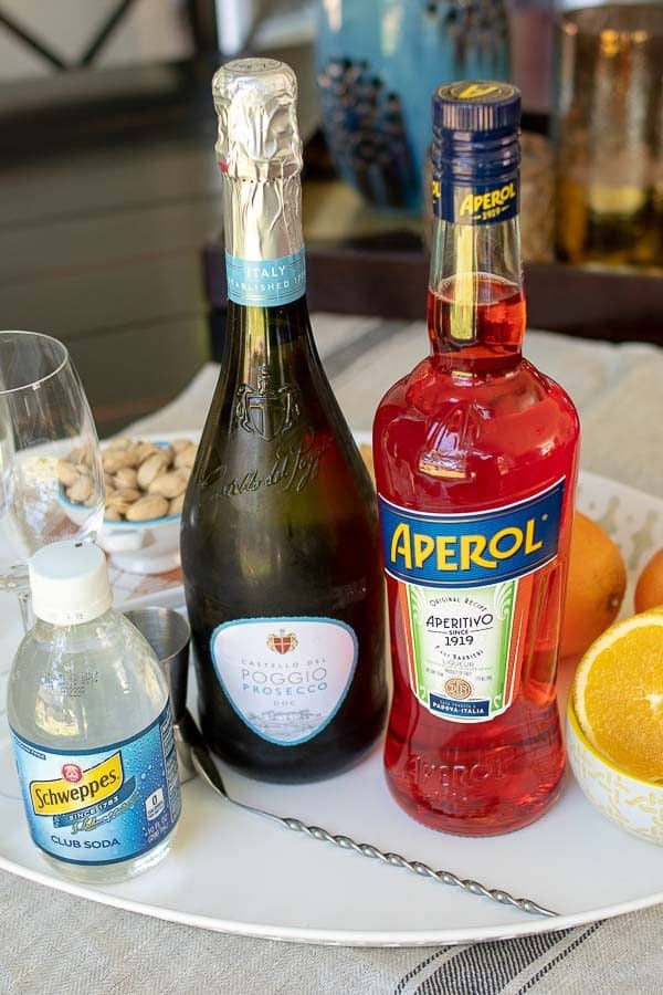 the ingredients for an Aperol spritz, Aperol, Prosecco, soda, and orange