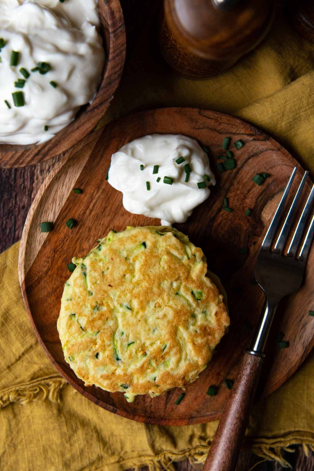 overhead shot of zucchini pancakes on a wood plate with a dollop of sour cream next to it
