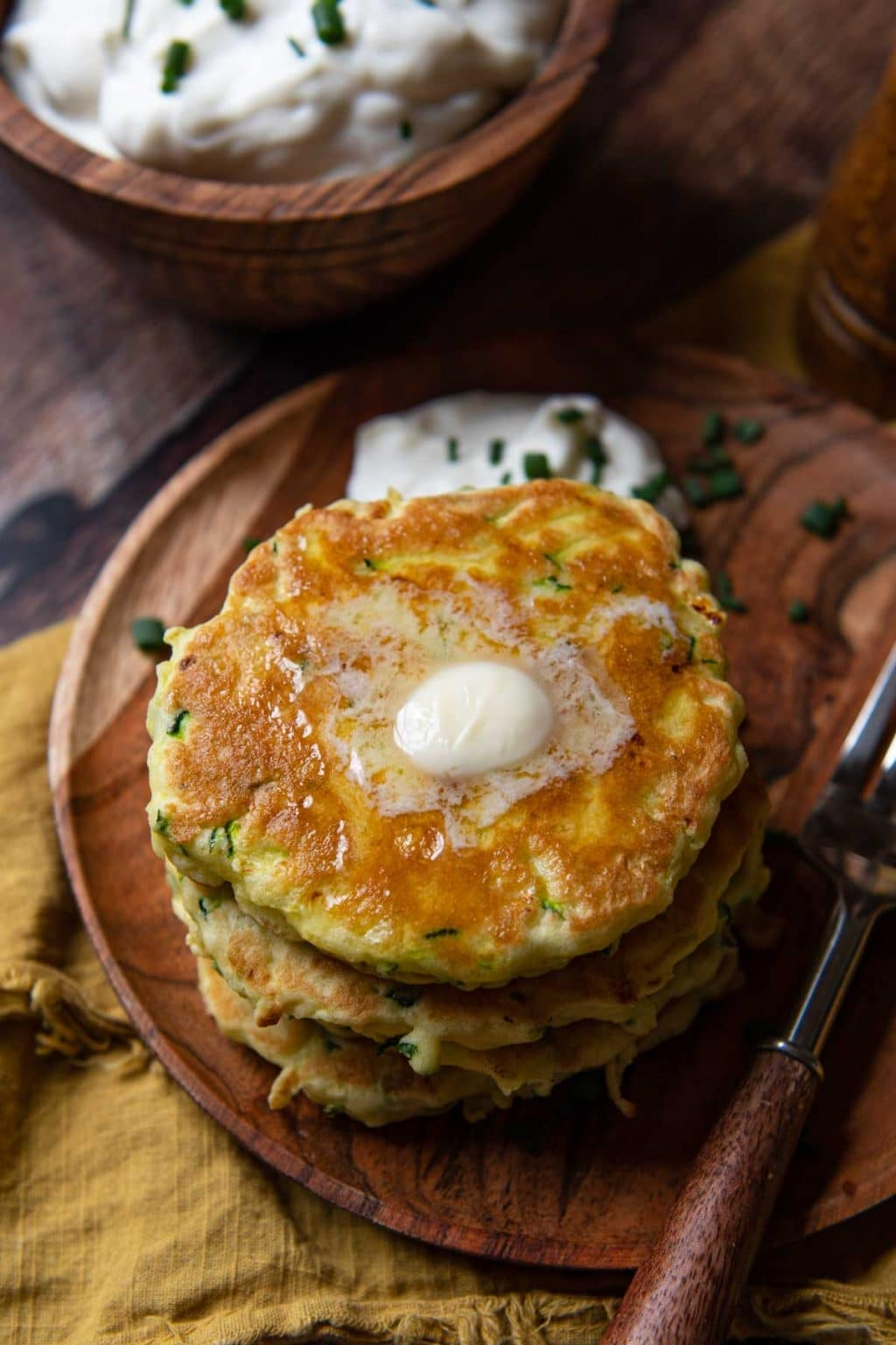 side angle of gluten-free zucchini fritters with melting butter on top