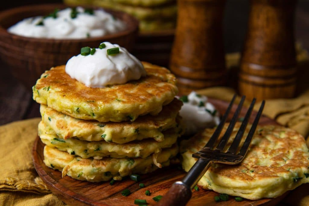 stack of zucchini fritters on a wood plate with a gold napkin underneath