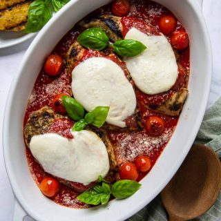 overhead shot of grilled chicken parmesan in a white oval dish with fresh basil leaves on top