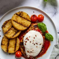 overhead shot of chicken parmesan with grilled polenta next to it on a white plate