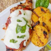 an overhead shot of grilled chicken parmesan on a white plate