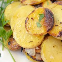 a close up of grilled potatoes on a white plate garnished with parsley