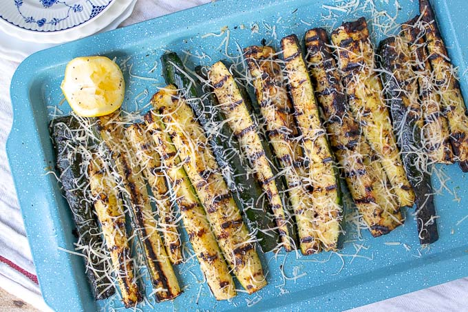 overhead shot of grilled zucchini on a blue baking sheet