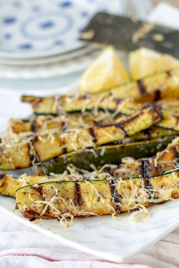 grilled zucchini lined up on a white plate