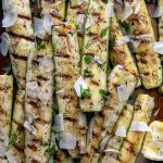 overhead shot of grilled zucchini and squash on a sheet pan with a serving utensil underneath