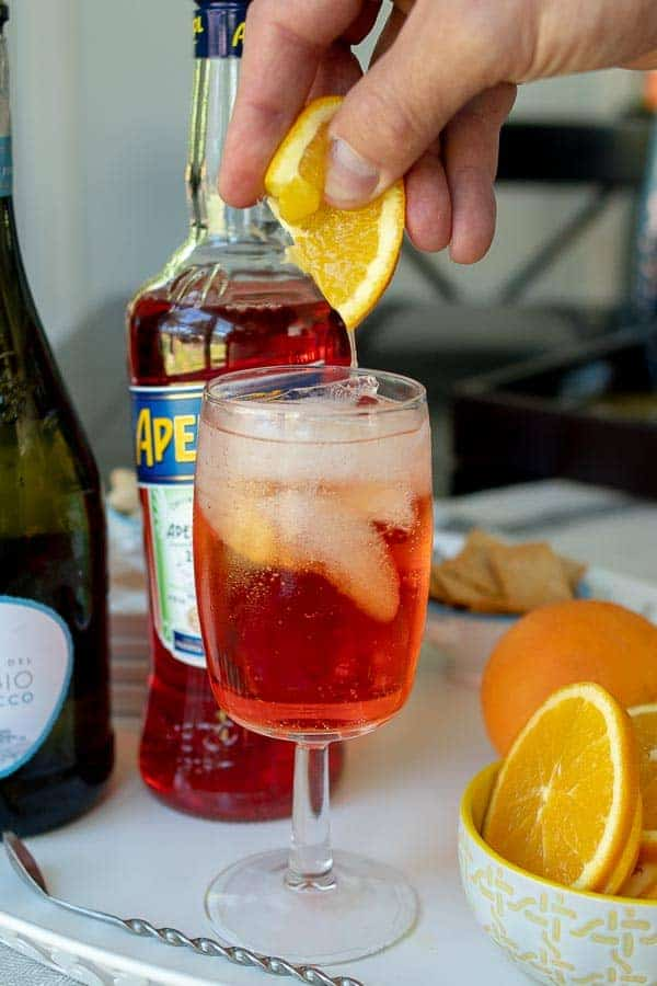 a fresh orange slice being squeezed into an Aperol spritz
