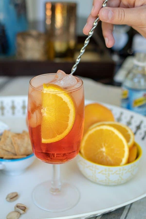 an Aperol spritz cocktail being stirred