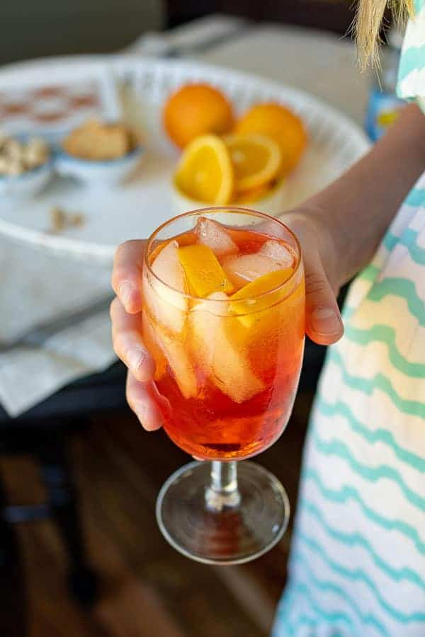 a hand holding up an Aperol spritz cocktail