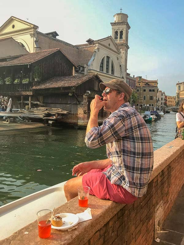 Ryan sitting on a ledge in Venice drinking an Aperol spritz