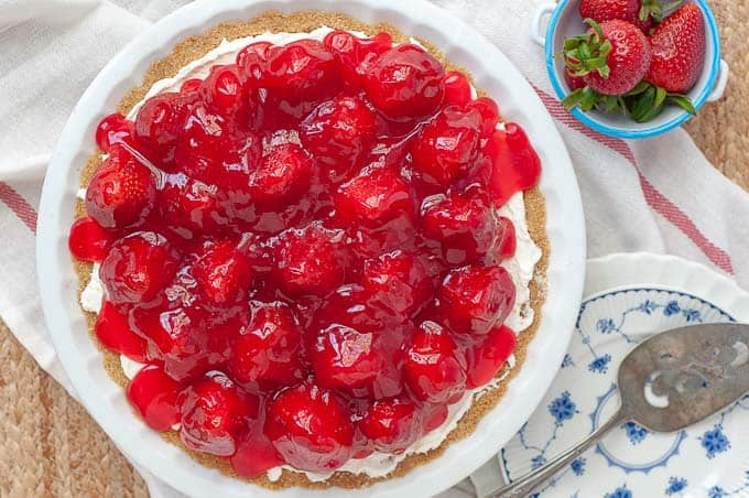 an overhead shot of no bake strawberry cheesecake with bowl of strawberries resting nearby