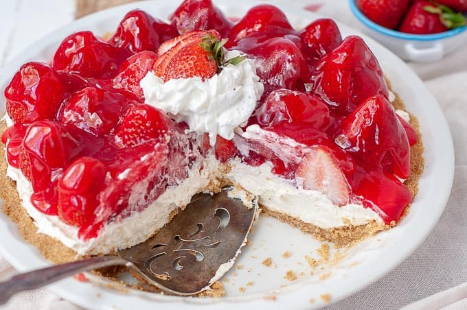 a dish with slices cut out of no bake strawberry cheesecake