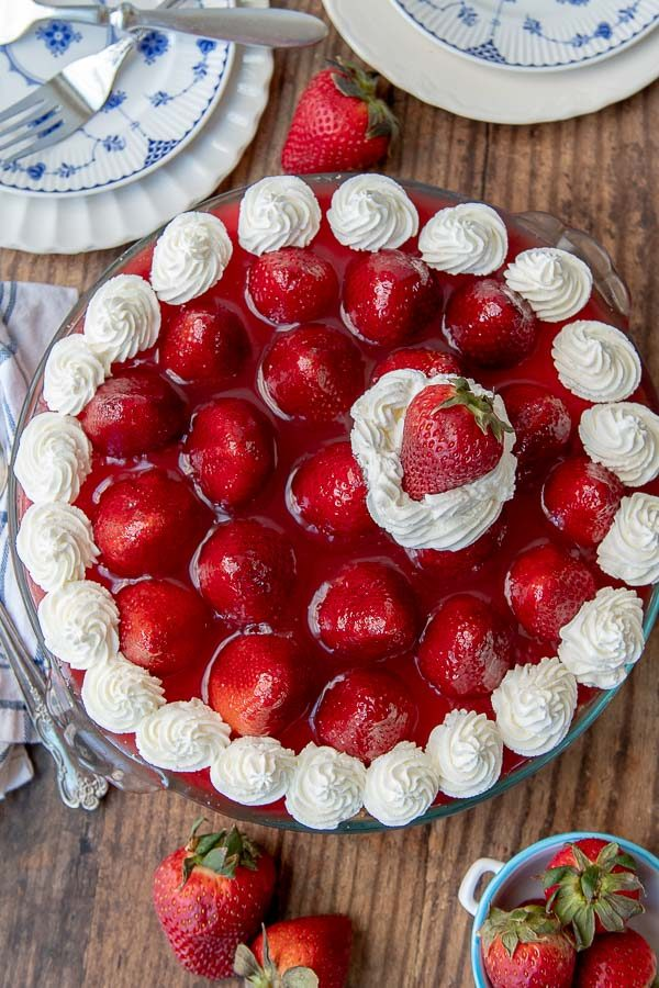 an overhead shot of no bake strawberry cheesecake with whipped cream dolloped on top
