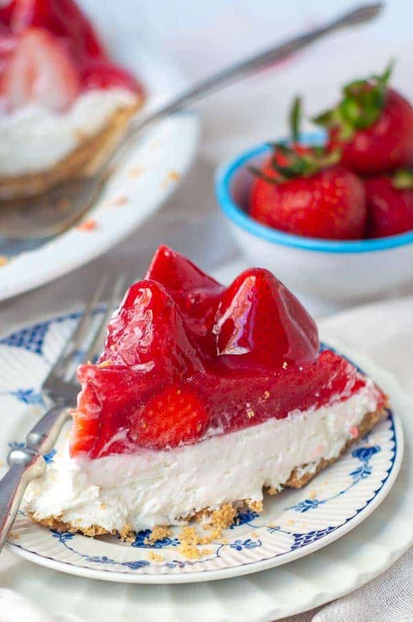 a slice of no bake strawberry cheesecake on a small white plate with fork resting on plate