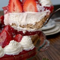 a slice of no bake strawberry cheesecake being lifted out a pie plate