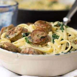 a bowl of creamy sausage pasta with a fork going in