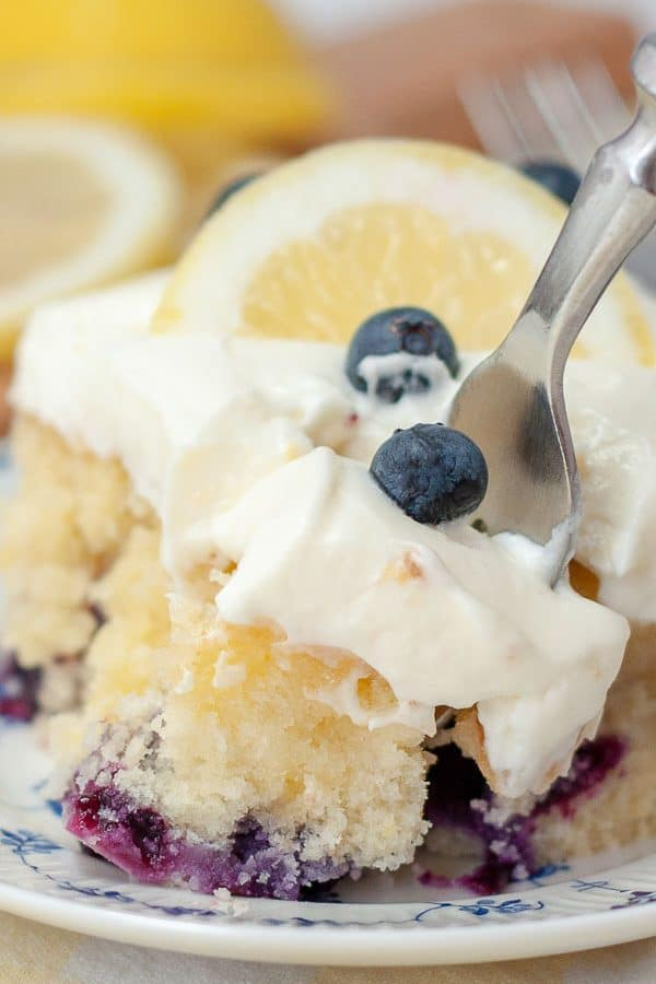 a close up shot of a fork diving into a slice of lemon blueberry cake