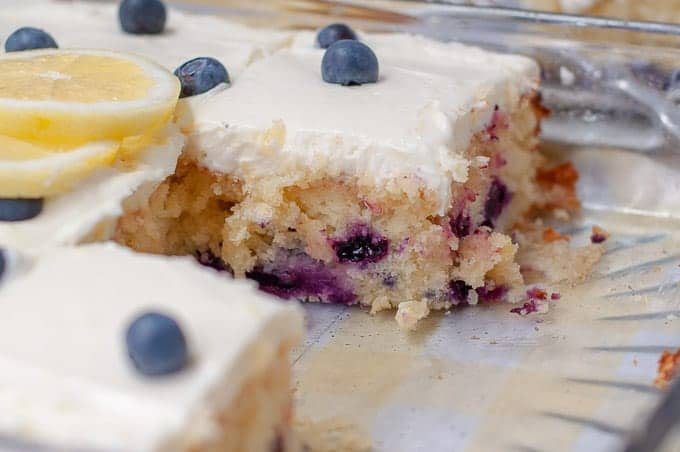 a close up shot of cut slices of lemon blueberry cake in a glass 9X13 pan