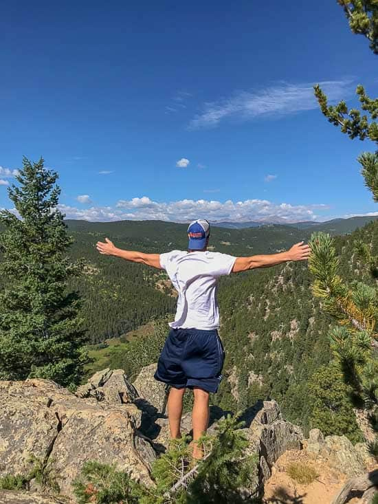 Ryan with his arms stretched wide on a mountain cliff