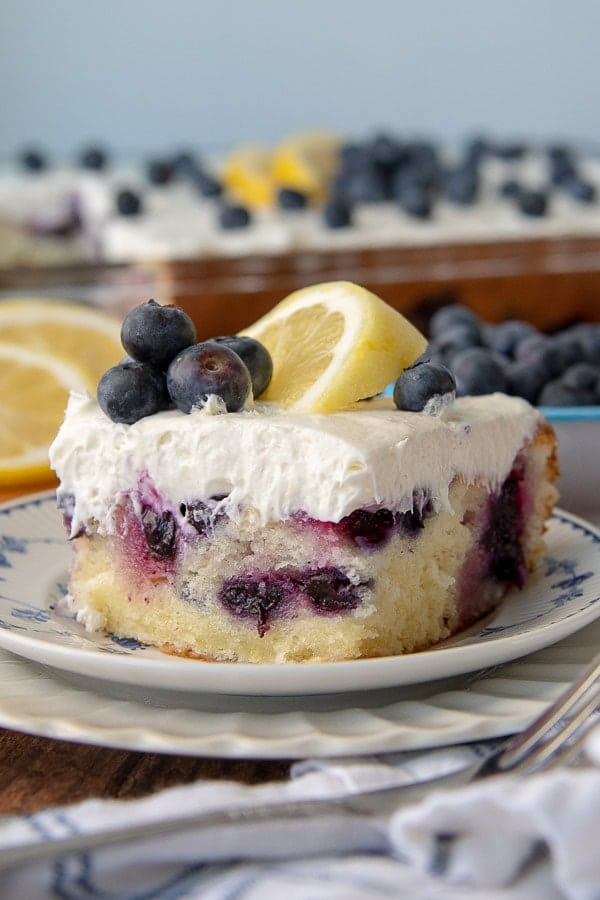 a close up of a cut piece of lemon blueberry cake on a stack of two plates