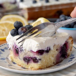 a fork cutting into a piece of lemon blueberry cake on a white plate with fresh blueberries on top