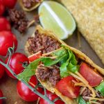 close up of beef taco with tomatoes, cheese, and lettuce