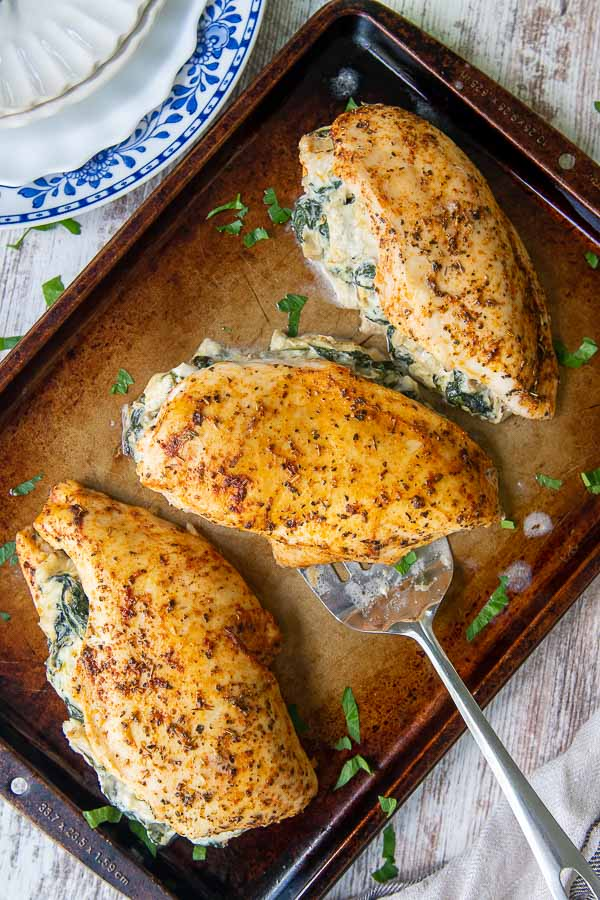 overhead shot of spinach stuffed chicken breasts on a baking sheet with a spatula under one