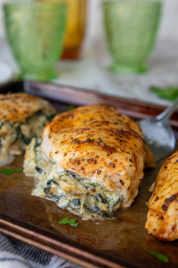 a close up of stuffed chicken breasts on a baking sheet with spinach artichoke filling