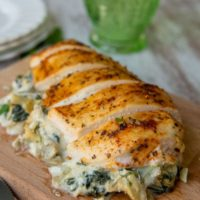 Spinach Stuffed Chicken Breast on a wooden cutting board with slices cut