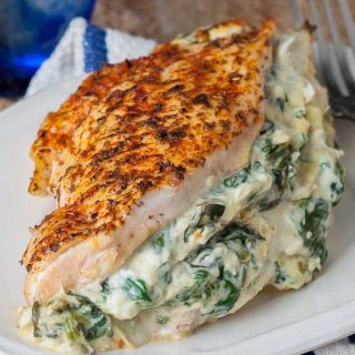a close up shot of spinach artichoke chicken on a white plate with a fork resting on the side