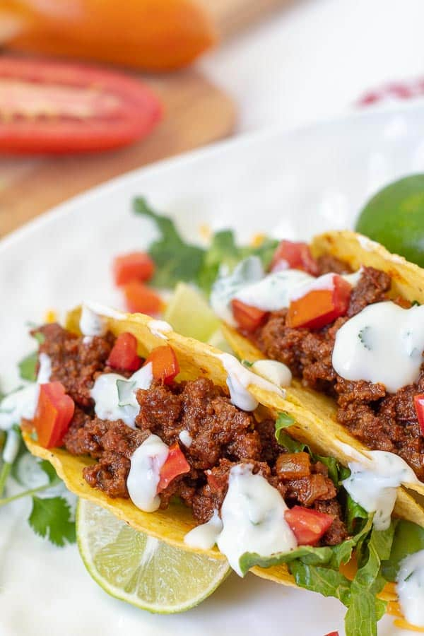 two tacos laying on a white plate with sour cream drizzled over top