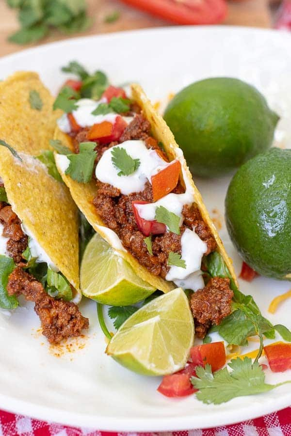 two tacos on a white plate with a couple limes resting next to it