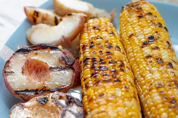 grilled peaches and corn on a blue plate