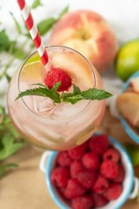 looking down on top of a raspberry peach mojito with fresh mint sprig and straw in the glass