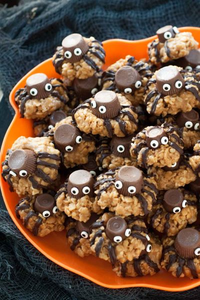a plate of gluten-free Halloween spider cookies on a orange plate