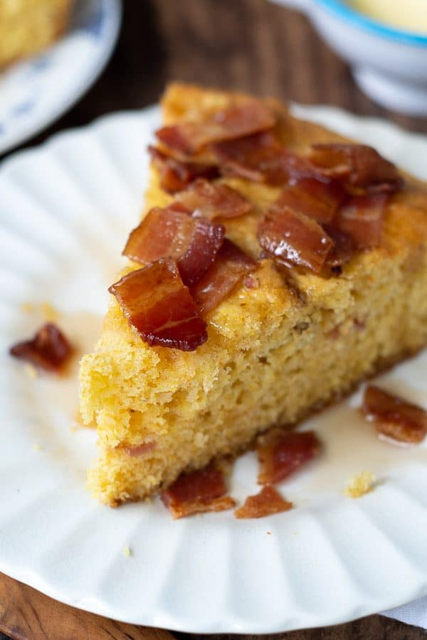 a wedge of bacon maple cornbread on a white plate with syrup drizzled over