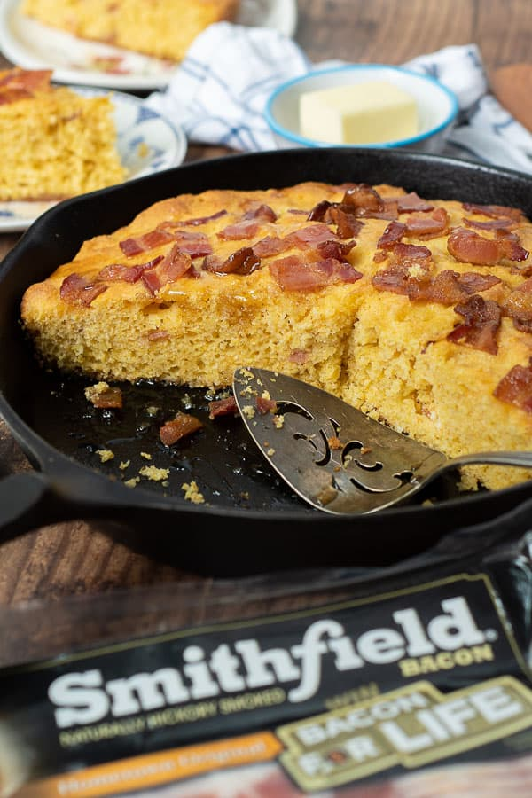 an iron skillet with slices of bacon cornbread cut out of it