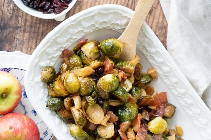 bacon brussels sprouts in a white serving bowl with a wooden spoon in it