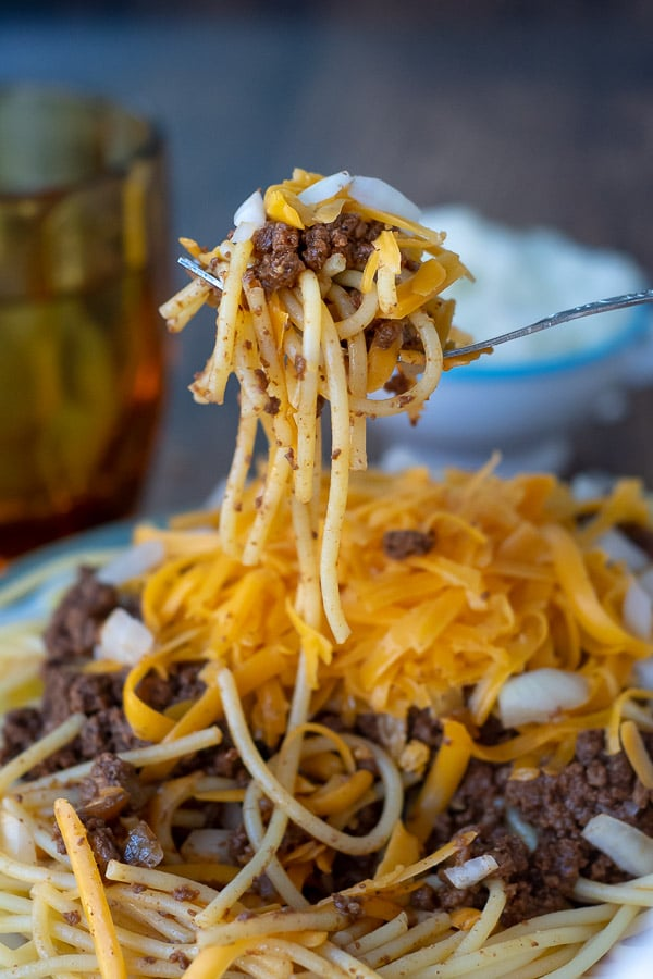 a fork holding up a bite of cincinnati chili with noodles hanging off