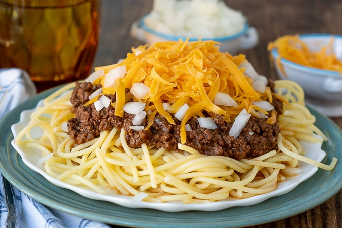 a plate of spaghetti with cincinnati chili sauce over top, lots of cheese, and onions