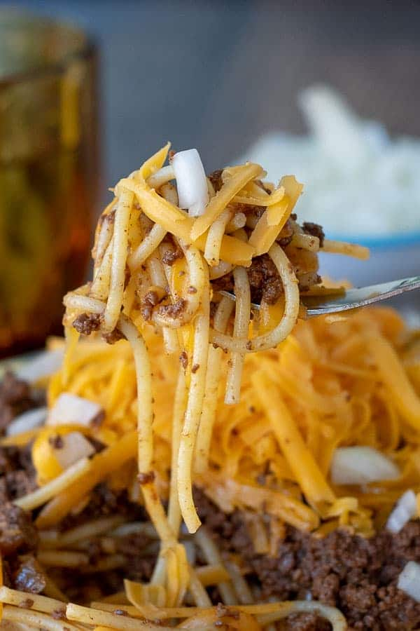 a bite of Cincinnati chili being lifted off a plate