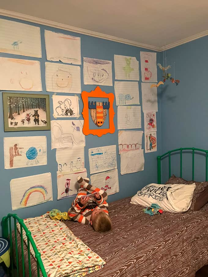 Elliot laying on his bed reading a book with artwork all over his wall