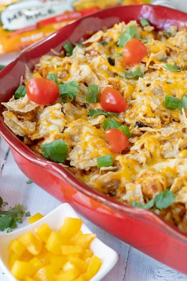 a close up side shot of mexican casserole with fresh tomatoes and cilantro on top