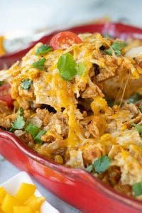 a wooden spoon lifting out Mexican chicken casserole from a casserole dish