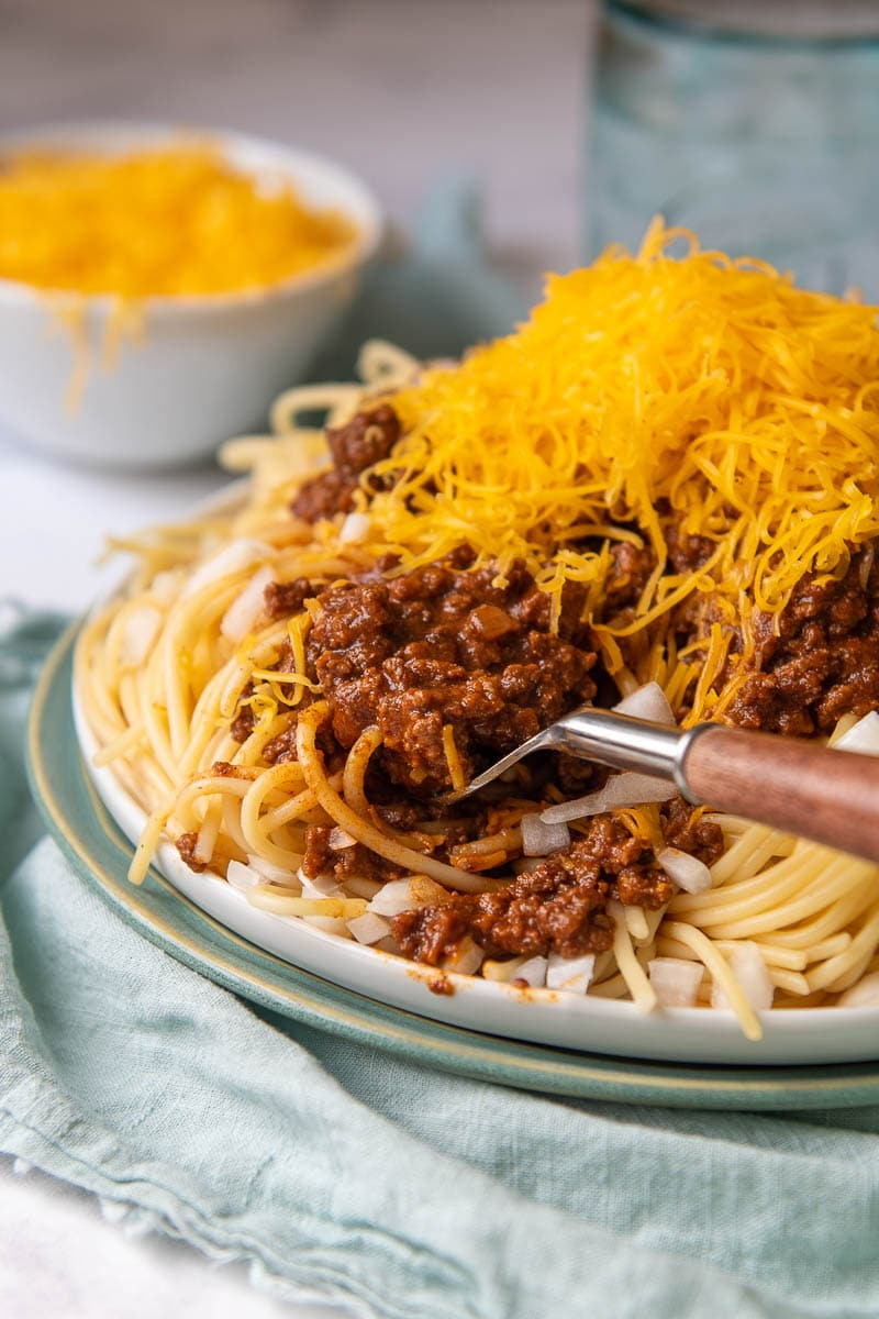 a fork going into chili topped spaghetti on a blue plate