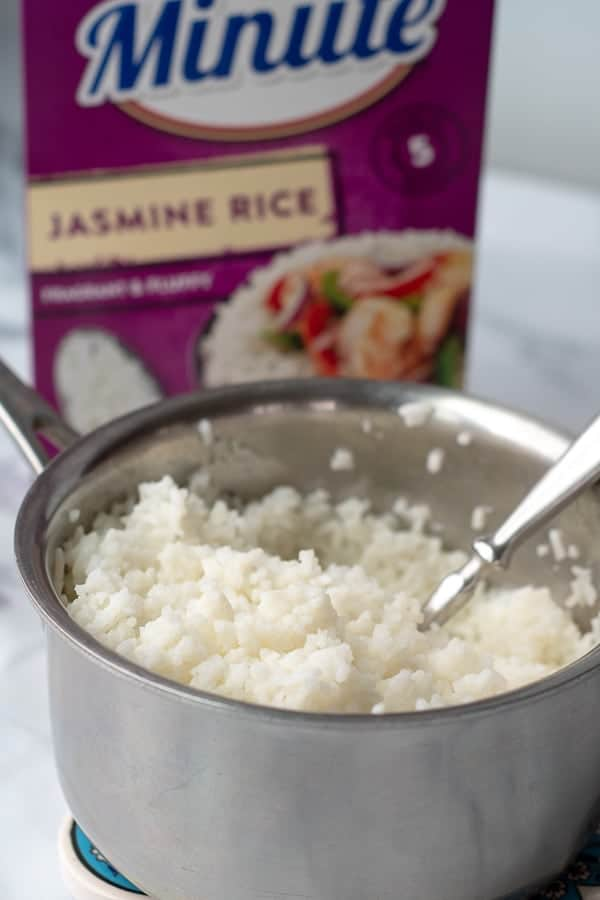 cooked jasmine rice in a pot with a box of Minute Jasmine Rice in background