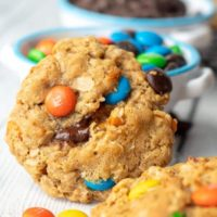 flourless kitchen sink cookie stood up by a bowl of m & ms