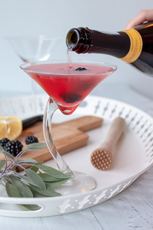 a bottle of Prosecco being pouring into a blackberry martini drink